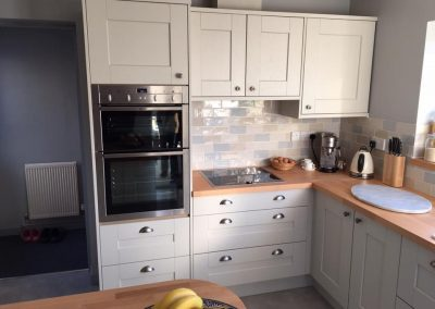 Painted Putty kitchen units with beech worktops